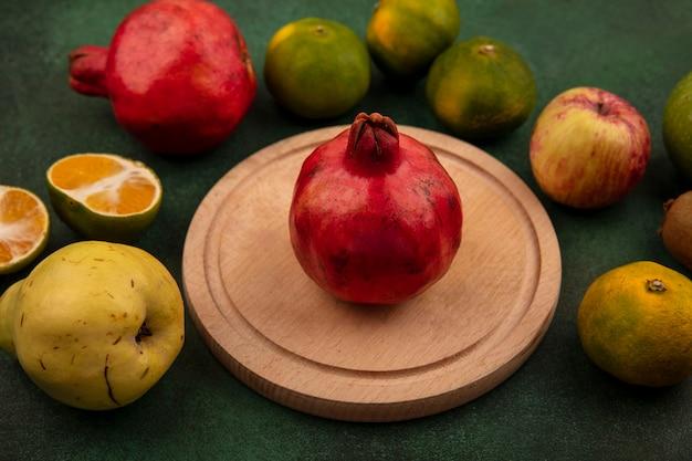 Melograno di vista frontale su un supporto con mandarini di pera e mela su una parete verde