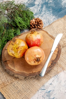 Front view pomegranates dinner knife on round tree wood cutting board pine tree branch on blue-white