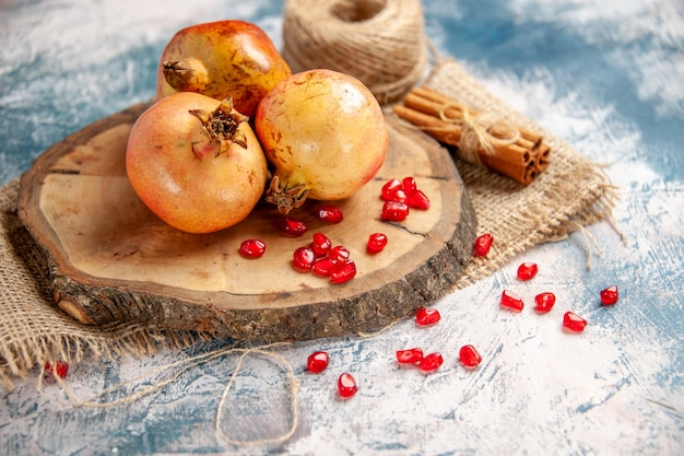 Front view pomegranates on round cutting board scattered pomegranate seeds cinnamon straw thread on blue-white