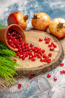 Front view pomegranates scattered pomegranate seeds in bowl on tree wood board on blue isolated background