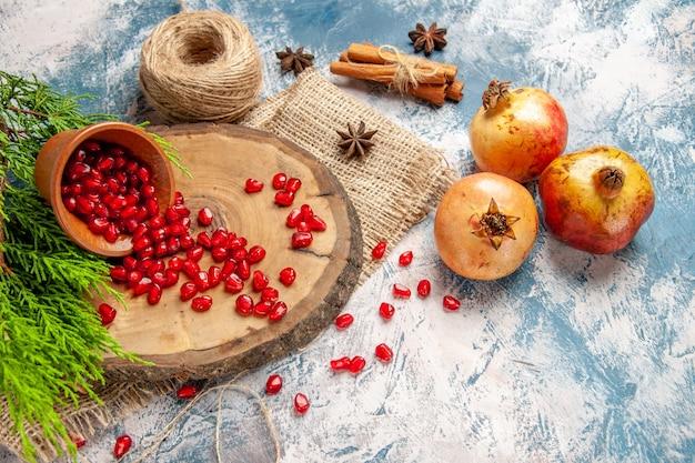 전면 보기 석류 흩어져 있는 석류 씨앗 나무 나무 보드에 그릇에 파란색 흰색 배경에 짚 스레드 계피 아니스 씨앗 무료 사진