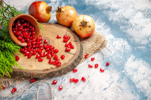 Front view pomegranates scattered pomegranate seeds in wooden bowl on round cutting board on blue-white free place
