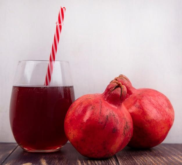 Гранаты, вид спереди со стаканом сока и красной соломкой