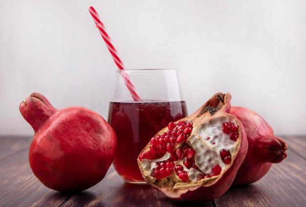 Melograni di vista frontale con un bicchiere di succo e una cannuccia rossa