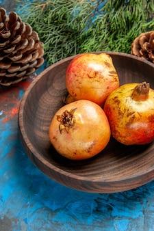 Melograni di vista frontale sul ramo e sui coni di legno del pino del piatto sul blu