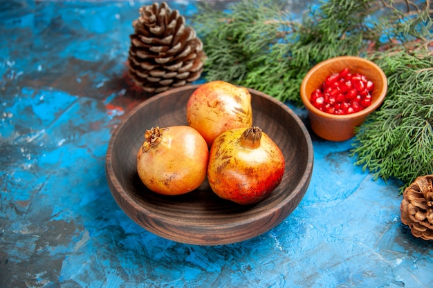Melograni di vista frontale sui semi di melograno del piatto di legno in ramo e coni di pino della ciotola di legno su blue