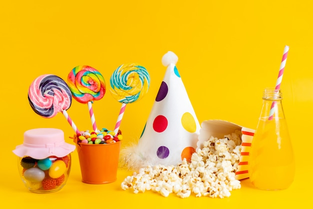 A front view popcorn and candies with birthday cap yellow cold cocktail on yellow