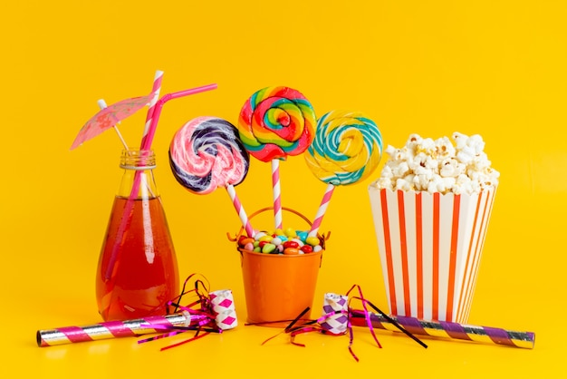 A front view popcorn and cocktail alongw with colorful candies and lollipops on yellow