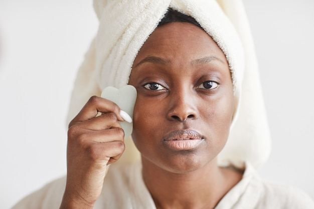 Front view portrait of beautiful african-american woman doing face massage while enjoying skincare routine at home and looking at camera, copy space