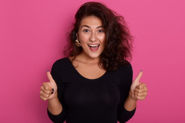 Front view portrait of beautiful young woman giving thumbs up standing isolated over rosy