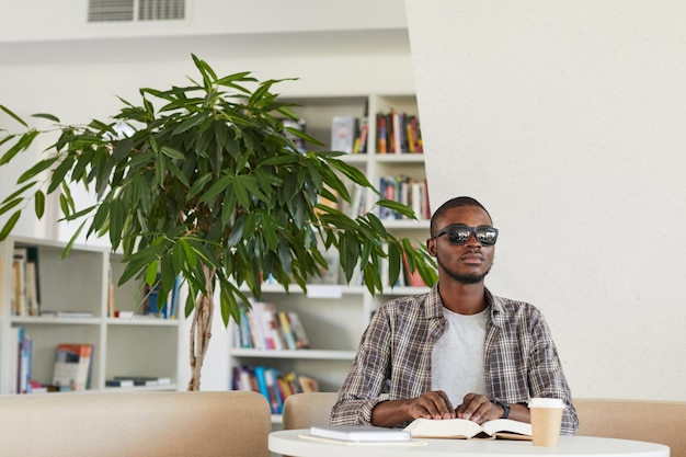 Front view portrait of blind african-american man reading braille book in library,