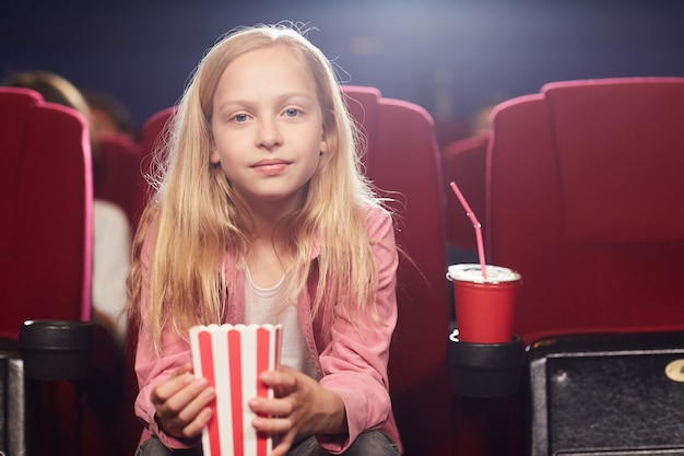 Front view portrait of blonde teenage girl looking at camera while holding popcorn cup in cinema theater, copy space