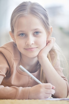Front view portrait of cute blonde girl smiling at camera while studying at home, hazy image lit by sunlight