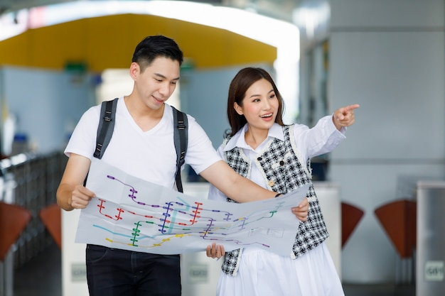 Front view portrait of cute smiling young adult asian lover travelers standing and looking paper metro map on vacations finding ways to tourist landmarks with a blurred skytrain station background