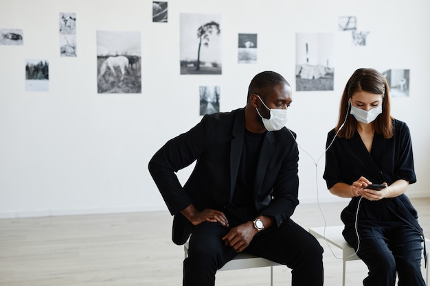 Front view portrait of elegant couple wearing masks while using smartphone with audio tour in modern art gallery, copy space