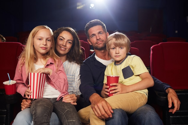 Front view portrait of happy family with two kids looking at camera while waiting to watch movie in cinema theater
