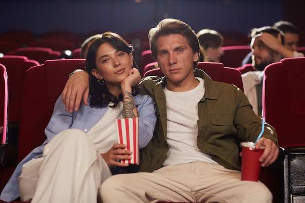 Front view portrait of loving young couple in cinema watching movie and holding popcorn while enjoying romantic date