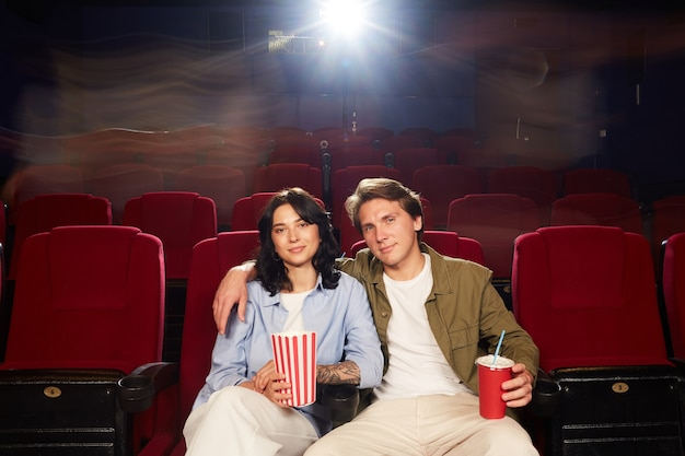 Front view portrait of loving young couple in embracing and looking at camera while waiting for movie in cinema theater, copy space