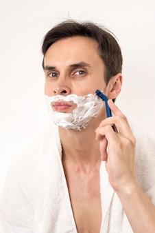 Front view portrait of man shaving