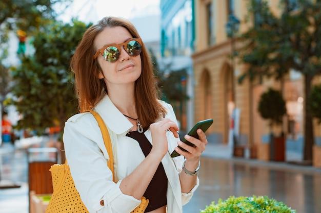 전면 뷰 초상화 현대 패션 행복한 여성 힙스터는 도시 거리에서 걷고 스마트 폰을 사용합니다.