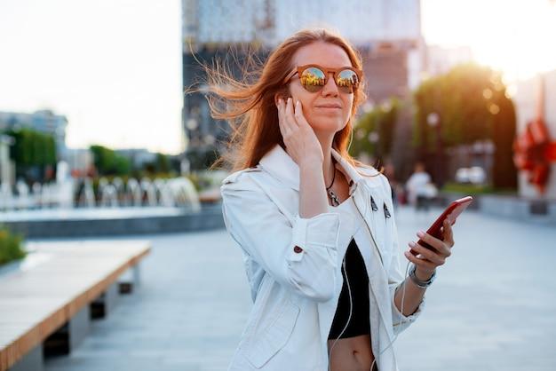 전면 뷰 초상화 현대 패션 행복한 여성 힙스터는 여름 햇살에 선글라스를 끼고 도시 거리에서 스마트 폰을 사용하여 걷고 있습니다. 인터넷, 온라인 서비스, 전화, 소녀, 여성