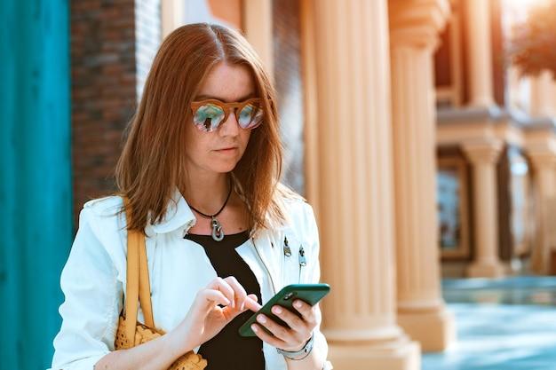 Вид спереди портрет современной моды счастливая женщина-хипстер идет и использует смартфон на городской улице в солнцезащитных очках