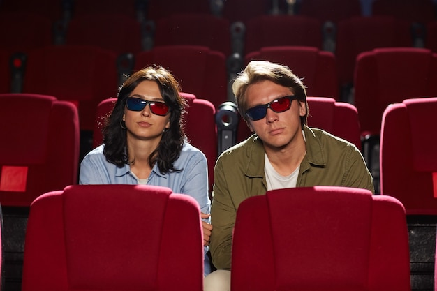 Front view portrait of modern young couple wearing stereo glasses while watching 3d movie in cinema theater, copy space