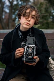 Front view portrait of non binary person holding a retro camera