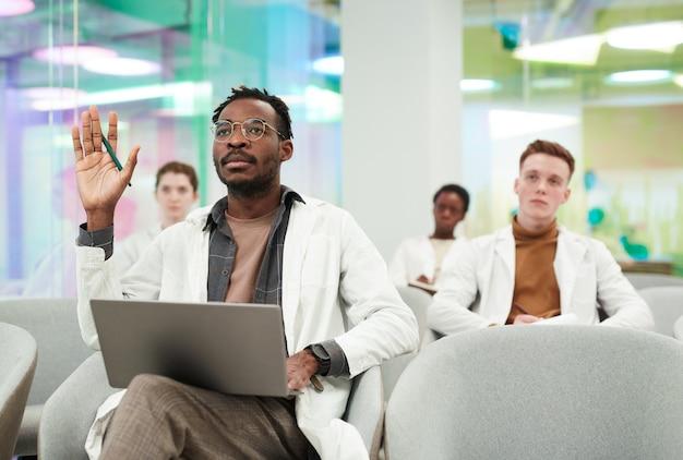 白衣を着て、聴衆に座って医学の講義を聞いている間に質問をする手を上げるアフリカ系アメリカ人の男性の正面図の肖像画