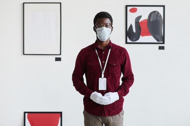 アートギャラリーで現代のグラフィック絵画に立ち向かいながらマスクを身に着けているアフリカ系アメリカ人の男性の正面図の肖像画、