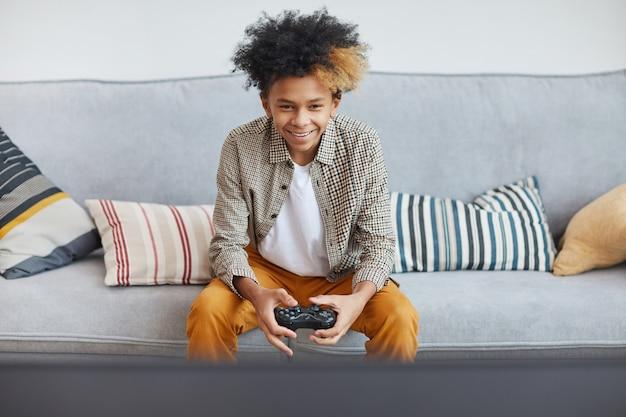 家でビデオゲームをプレイし、ゲームパッド、コピースペースを保持している興奮したアフリカ系アメリカ人の少年の正面図の肖像画