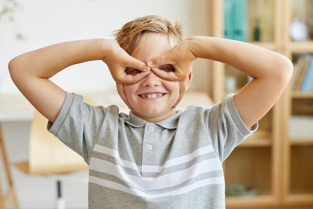 家のインテリアでマスクを身に着けているスーパーヒーローのふりをしてカメラで顔を作る幸せな少年の正面の肖像画