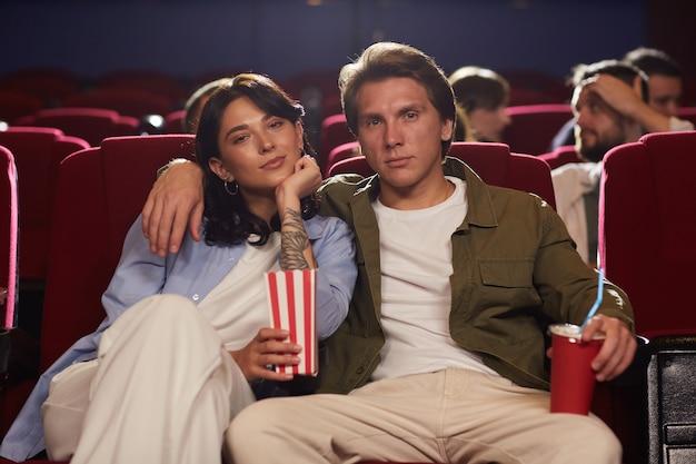 Портрет вид спереди влюбленной молодой пары в кино, смотрящей фильм и держащей попкорн, наслаждаясь романтическим свиданием