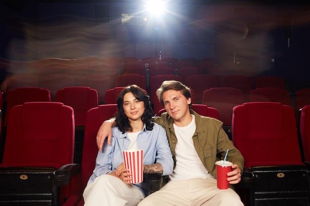 Портрет вид спереди любящей молодой пары в обнимку и глядя в камеру в ожидании фильма в кинотеатре, копией пространства