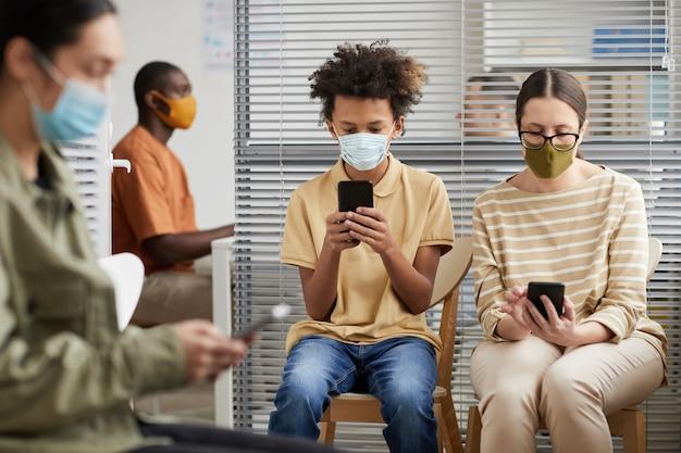 Портрет вид спереди многоэтнической группы людей, использующих смартфоны в очереди в медицинской клинике, все в масках