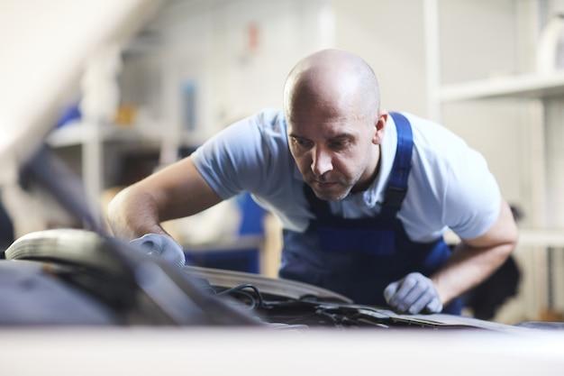 ガレージショップ、コピースペースでの検査中に車両の開いたボンネットを覗き込んでいる筋肉の自動車整備士の正面図の肖像画