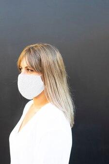 Портрет вид спереди серьезной женщины с защитной маской, избегающей заражения, смотрящей на обочину улицы