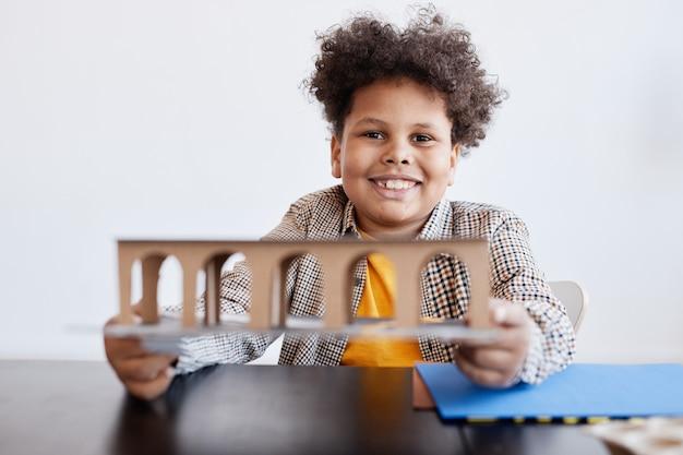 手作りの学校プロジェクト、コピースペースに取り組んでいる間、段ボールのモデルを保持している笑顔のアフリカ系アメリカ人の少年の正面図の肖像画