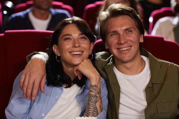 Портрет вид спереди улыбающейся молодой пары в кино, смотрящей фильм и обнимающейся, наслаждаясь романтическим свиданием