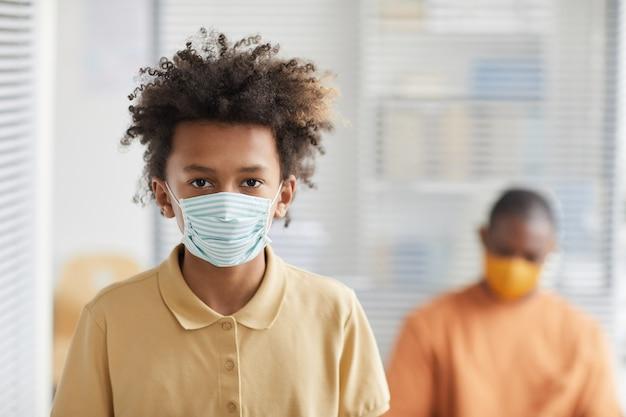 Портрет вид спереди афроамериканского мальчика-подростка в маске и смотрящего в камеру во время ожидания в очереди в медицинской клинике, копией пространства