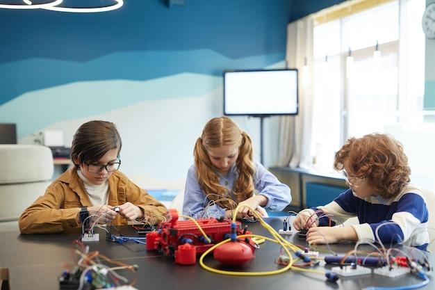 Портрет трех симпатичных детей, строящих роботов, во время инженерных занятий в школе развития, вид спереди, копировальное пространство