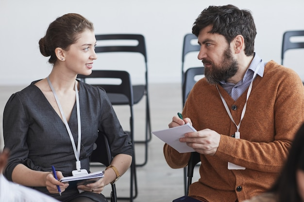 Портрет вид спереди двух человек в аудитории на бизнес-конференции, мужчина и женщина разговаривают и делают заметки, сидя на стульях в ряд