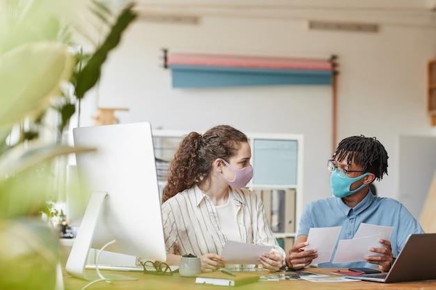 사무실 스튜디오에서 책상에서 사진을 검토하는 동안 마스크를 쓰고 두 젊은 사진 작가의 전면보기 초상화, 복사 공간