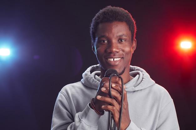 Портрет вид спереди молодого афроамериканца, поющего в микрофон и улыбающегося, стоя на сцене в свете, копией пространства