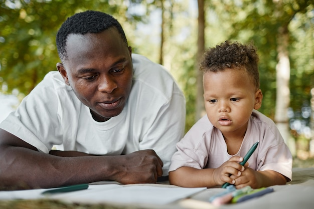 Портрет вид спереди молодого афроамериканского отца, играющего с милым сыном в парке, лежа на траве