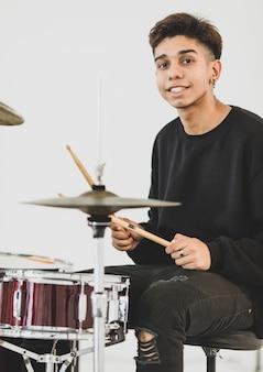음악을 연주하는 10대 드러머의 전면 뷰 초상화. 카메라를 보고 웃으면서 드럼을 연주하는 젊은 음악가. 흰색 배경으로 악기를 연주하는 주니어 학생