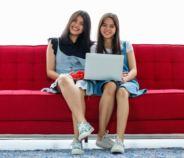 赤いソファに座ってデジタルノートパソコンで映画を見ている魅力的な笑顔の若いタイ・トルコのティーンエイジャーの正面のポートレートショット。家で一緒に暮らす混血姉妹の概念