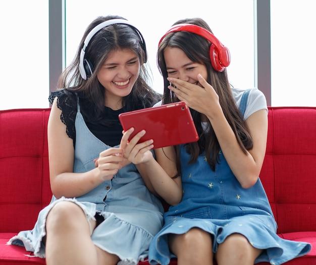 赤いソファに座って、赤いタブレットで映画を見て、大声で笑っている若いタイ・トルコのティーンエイジャーの正面のポートレートショット。家で一緒に暮らす混血姉妹の概念