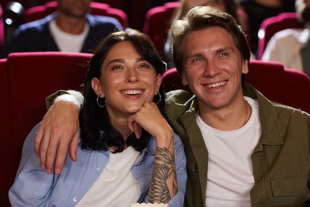 Front view portrait of smiling young couple in cinema watching movie and embracing while enjoying romantic date