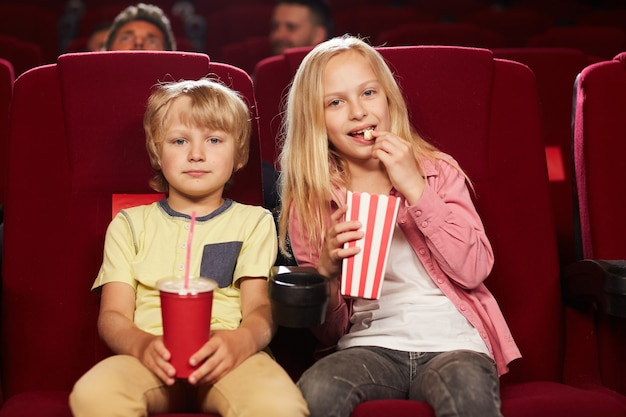 Front view portrait of two cute kids watching movie in cinema theater and eating popcorn, copy space